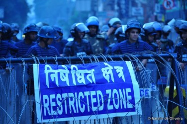 Photo: A police blockade around the demonstrations. A protestor among the crowds in Kathmandu. Credit: Natalie de Oliveira