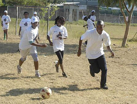 Photo of Tico Tico dribbling a football with children following