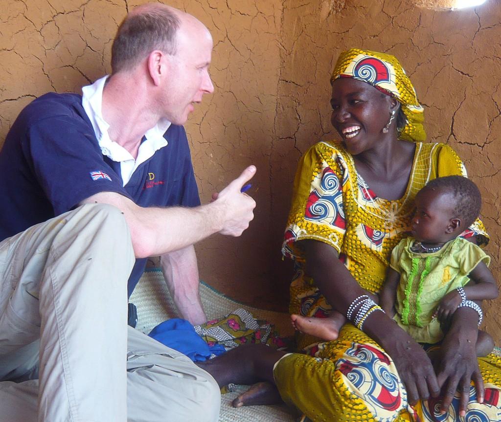 Photo of Colum talking to Aisha and her child
