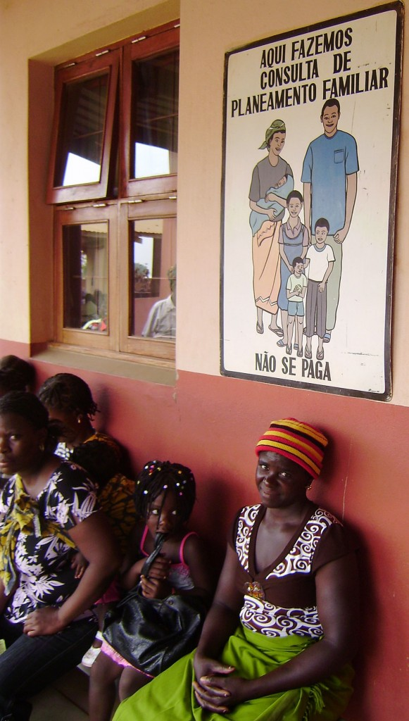 Photo of women sitting waiting under a poster