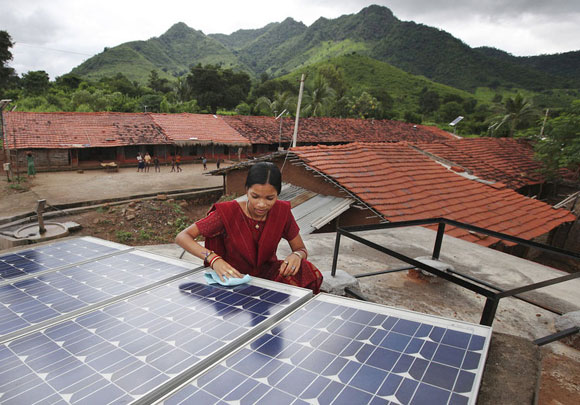 Photo of a woman wiping solar panels
