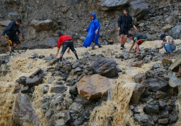 Image: Villagers try to rebuild a flooded road