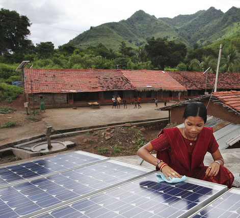 Photo: woman wiping a solar panel
