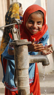 Photo of a girl drinking at a water pump