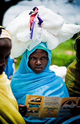 A woman carries a bednet on her head