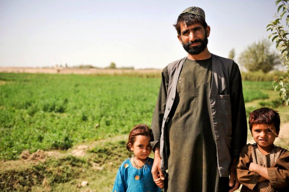 An Afghan farmer stands with his children at a farm in Lashkar Gah