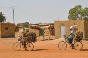 Two women cycling with wood on their bikes