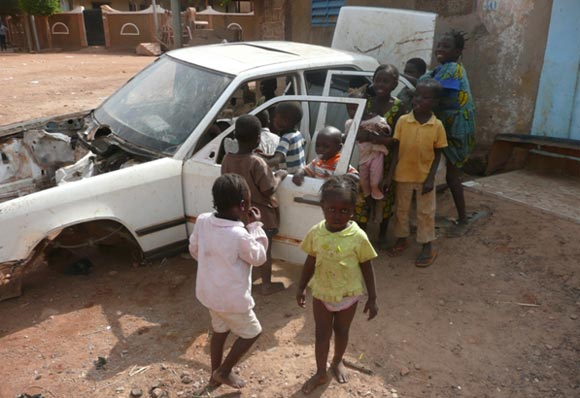 Children play in an abandoned car