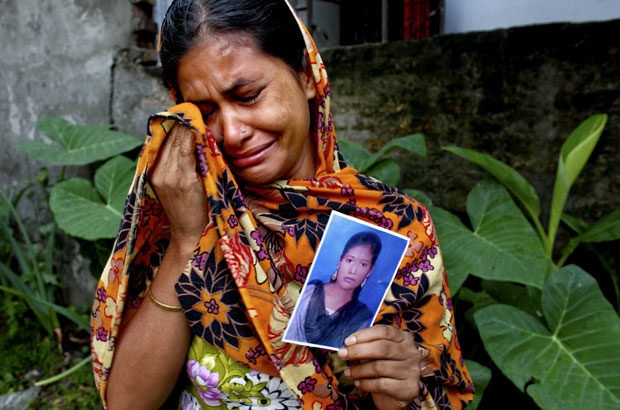 The mother of 18 year old Aleyais cries and holds a picture of her daughter who is believed to be among the victims of the collapse of the Rana Plaza complex in Savar on the outskirts of Dhaka.