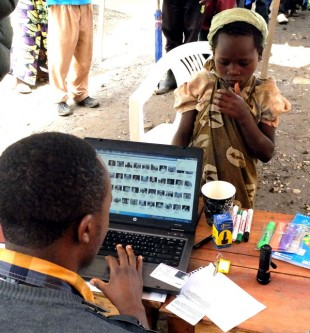 A young recipient has her ID checked on the database. Picture: Chris Pycroft/DFID DRC