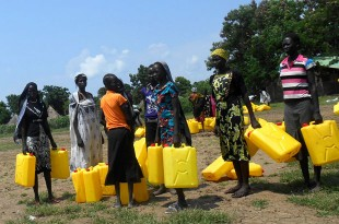 Over 100 women arrive with Jerry cans to collect water for families and people with disabilities in the local community. Picture: Ian Hughes/FCO