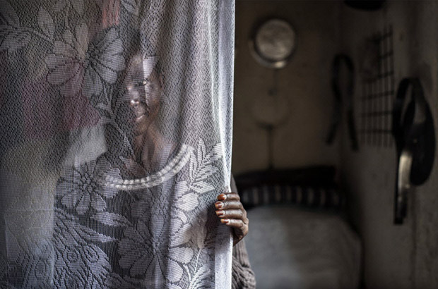 A young Somali woman hides herself behind a curtain. Picture: Sven Torfinn/Panos