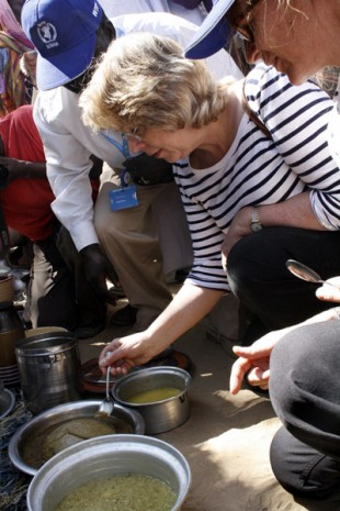 Baroness Northover tastes some of the sample dishes prepared by the women. Picture: Vicky Seymour/DFID