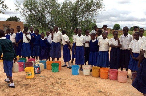 Young girls in uniforms lining up to collect water at Mphangwe's main water point. Picture: Lindsay Northover/DFID