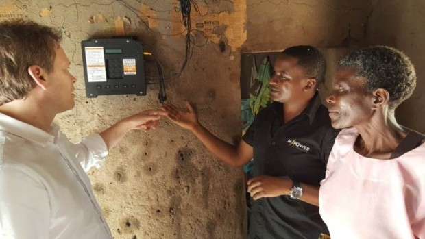 Elizabeth showing Grant Shapps the M-Power system, with Erick from Off-Grid Electric. Picture: Vel Gnanendran/DFID