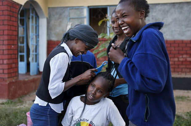 Eunice, 13, helps braid the hair of another resident. In Kenya, girls are most vulnerable to FGM and forced marriage during the school holiday breaks. Picture: Newsha Tavakolian for TooYoungToWed/The Girl Generation.